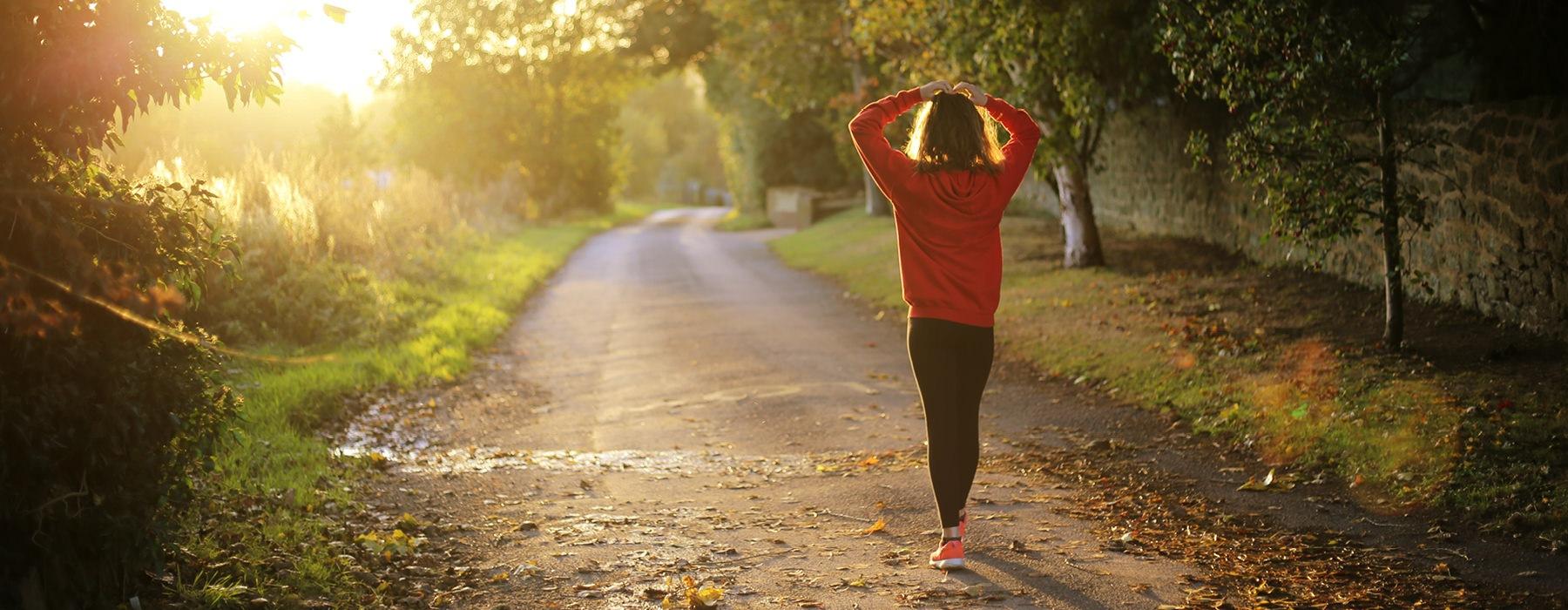 woman in sweats, walking down a country dirt road toward the setting sun